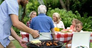 Gelukkige familie die barbecue samen doen stock footage
