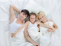 Gelukkige familie die in bed ligt Stock Afbeelding