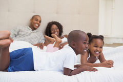 Gelukkige familie die bij bed het glimlachen liggen Royalty-vrije Stock Foto's