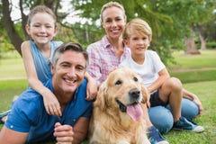 Gelukkige familie die bij de camera met hun hond glimlachen Royalty-vrije Stock Foto