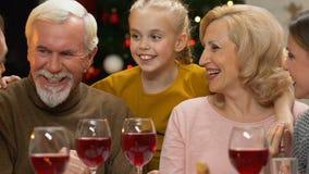 Gelukkige familie die bij Kerstmisdiner gekscheren, traditie om te zijn allen samen op vakantie stock video