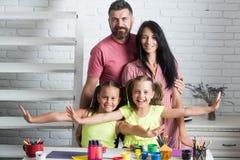 Gelukkige familie die bij lijst met kleurrijke verven glimlachen stock afbeelding