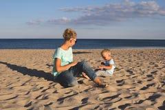 Gelukkige familie die bij strand in de zomer rusten Stock Afbeelding