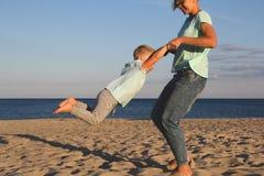 Gelukkige familie die bij strand in de zomer rusten Stock Foto's