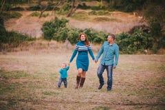 Gelukkige familie die in blauwe modieuze kleren in de herfstbos lopen royalty-vrije stock afbeelding