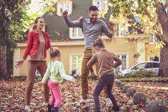 Gelukkige familie die buiten spelen Ouders met dochters Stock Fotografie