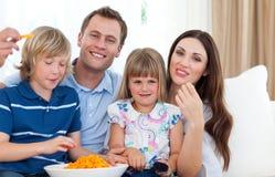 Gelukkige familie die chips eet Stock Foto's