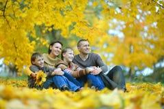 Gelukkige familie die in de herfstpark liggen Royalty-vrije Stock Afbeeldingen