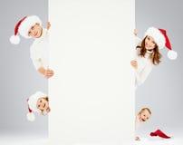 Gelukkige familie die in de hoeden van de Kerstman Kerstmis wacht Stock Afbeeldingen