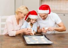 Gelukkige familie die in de hoeden van de santahelper koekjes maken Royalty-vrije Stock Afbeeldingen