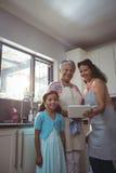 Gelukkige familie die digitale tablet in keuken gebruiken Stock Afbeeldingen