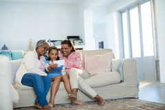 Gelukkige familie die digitale tablet in woonkamer gebruiken Royalty-vrije Stock Fotografie