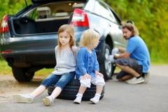 Gelukkige familie die een autowiel veranderen Stock Afbeeldingen