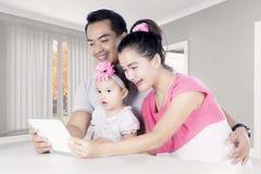 Gelukkige familie die een digitale tablet thuis gebruiken Stock Foto's