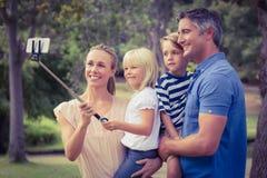 Gelukkige familie die een selfiestok in het park gebruiken stock foto