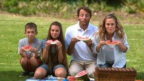 Gelukkige familie die een watermeloen eten terwijl het hebben van een picknick stock videobeelden