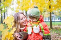 Gelukkige familie die en de herfstbladeren glimlachen houden Royalty-vrije Stock Foto