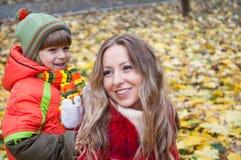Gelukkige familie die en de herfstbladeren glimlachen houden Stock Afbeeldingen