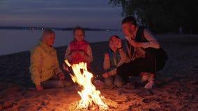 Gelukkige familie die en door brand tijdens picknick op nachtstrand eten spreken stock videobeelden