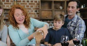 Gelukkige Familie die Gezond Diner samen in Keukenouders koken en Kinderen die terwijl het Voorbereiden van Maaltijd spreken stock videobeelden