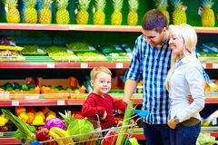 Gelukkige familie die gezond voedsel in supermarkt kopen Stock Afbeelding