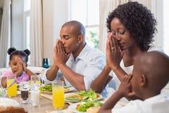 Gelukkige familie die gunst zeggen vóór maaltijd royalty-vrije stock foto