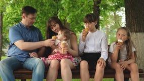 Gelukkige familie die in het park loopt Kinderen en ouders De kinderen met ouders zitten in park op bank etend ijs stock footage