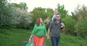Gelukkige familie die in het park na het winkelen lopen stock video