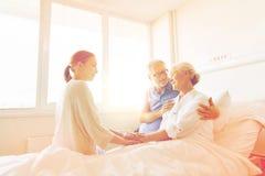 Gelukkige familie die hogere vrouw bezoeken bij het ziekenhuis royalty-vrije stock foto