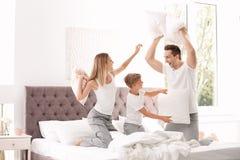 Gelukkige familie die hoofdkussenstrijd op bed hebben stock afbeeldingen