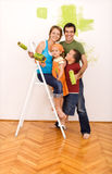 Gelukkige familie die hun nieuw huis samen schildert royalty-vrije stock afbeelding
