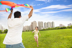 Gelukkige familie die kleurrijke vlieger in het stadspark speelt Stock Afbeeldingen