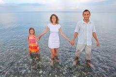 Gelukkige familie die knie-zichdiep in overzees op strand bevindt Stock Foto
