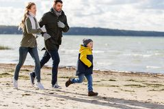 Gelukkige familie die langs de herfststrand lopen royalty-vrije stock afbeelding