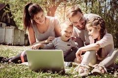 Gelukkige familie die laptop met behulp van, die op het groene gras zitten Royalty-vrije Stock Afbeelding