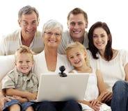 Gelukkige familie die laptop thuis met behulp van Stock Foto