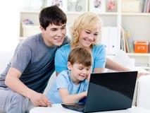 Gelukkige familie die laptop thuis met behulp van Stock Foto's