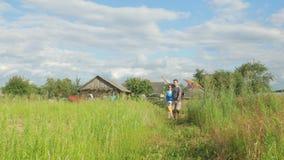 Gelukkige familie die met een vlieger op groen gras aan de camera lopen Moeder, vader en baby 2 jaar in de zomer stock video