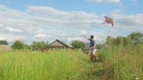 Gelukkige familie die met een vlieger op groen gras aan de camera lopen Moeder, vader en baby 2 jaar in de zomer stock footage
