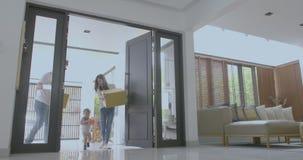 Gelukkige familie die met jonge geitjes dozen houden die nieuw modern huis ingaan stock footage