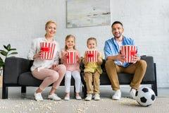 gelukkige familie die met popcorndozen bij bank en het glimlachen zitten stock afbeeldingen