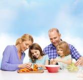 Gelukkige familie die met twee jonge geitjes diner thuis maken Royalty-vrije Stock Fotografie