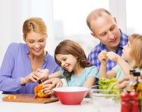 Gelukkige familie die met twee jonge geitjes diner thuis maken Stock Afbeeldingen