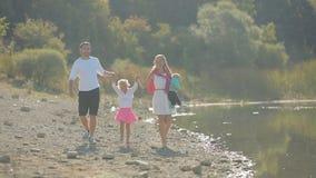 Gelukkige familie die met twee jonge geitjes langs de kust lopen stock videobeelden
