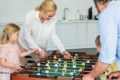 gelukkige familie die met twee jonge geitjes lijstvoetbal samen spelen royalty-vrije stock afbeeldingen