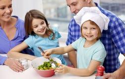 Gelukkige familie die met twee jonge geitjes thuis koken Stock Afbeeldingen
