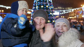 Gelukkige familie die nieuw jaar in het stadsvierkant vieren Iedereen bekijkt de camera en de glimlach Tegen de achtergrond is stock footage