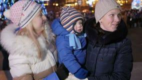 Gelukkige familie die nieuw jaar in het stadsvierkant vieren Iedereen bekijkt de camera en de glimlach Tegen de achtergrond is stock video