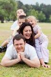 Gelukkige familie die omhoog op het park wordt opgestapeld stock foto
