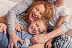 Gelukkige familie die op bed thuis liggen royalty-vrije stock foto